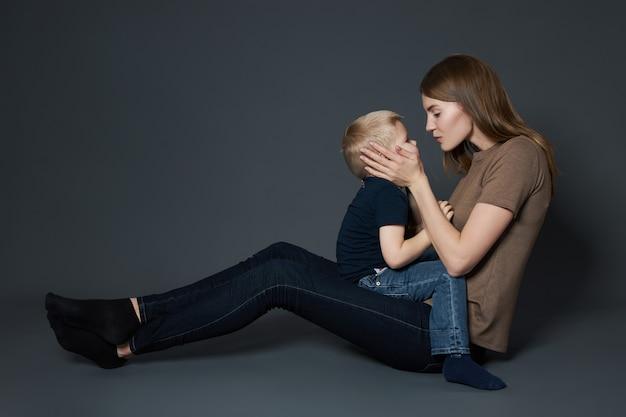 若い母親は幼い息子を抱きしめてキスします。女性が子供を抱きしめる