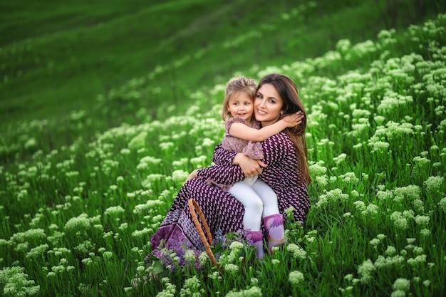 若い母親は、花が咲く牧草地に座りながら娘を抱きしめる