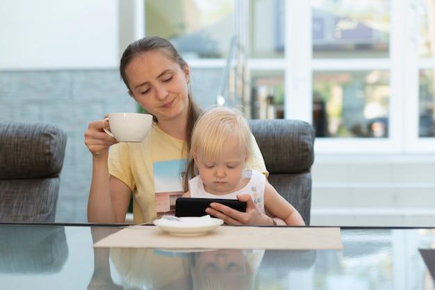 彼女の腕の中で子供と一緒にカフェの若い母親はコーヒーを飲み、電話を見ます。現代のビジネスママ。