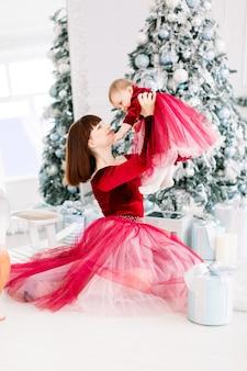 빨간 드레스에 젊은 어머니는 크리스마스 트리 근처에 앉아 그녀의 귀여운 작은 딸을 보유