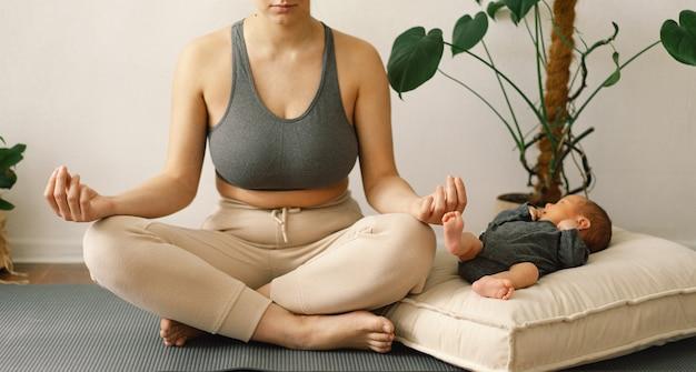 Молодая мать в спортивной одежде тренируется с новорожденным сыном дома
