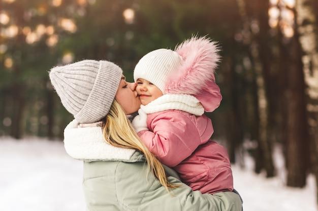 冬の若い母親は、幼い娘を抱きかかえてキスをします。家族写真。母性と子供時代