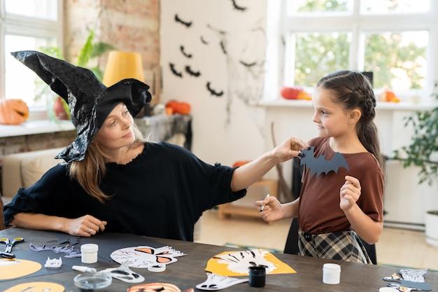 Молодая мать в платье ведьмы сидит за столом с фотографиями на хэллоуин и создает костюм дочери для вечеринки на хэллоуин