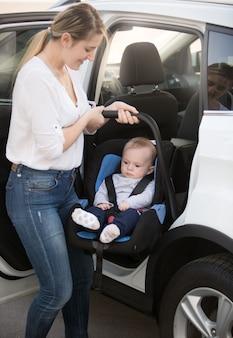 Молодая мать, устанавливающая детское автокресло с ребенком