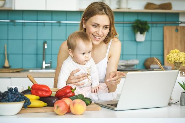 若い母親は、調理し、モダンなキッチンの設定で彼女の赤ん坊の娘と遊んでいます。ノートパソコンを見て、笑みを浮かべてください。