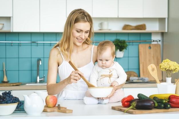 若い母親は、調理し、モダンなキッチンの設定で彼女の赤ん坊の娘と遊んでいます。