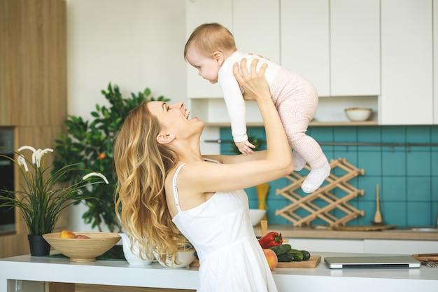 Молодая мать готовит и играет с дочерью в современной кухне.