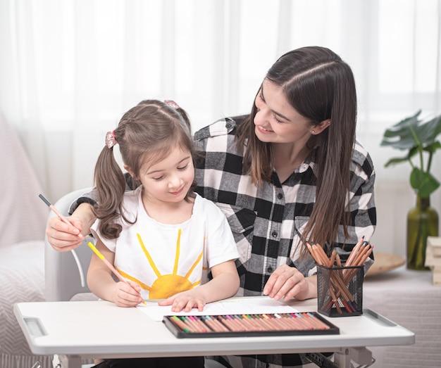 젊은 어머니는 작은 귀여운 딸과 함께 숙제를하고 있습니다. 홈 스쿨링 및 교육 개념.