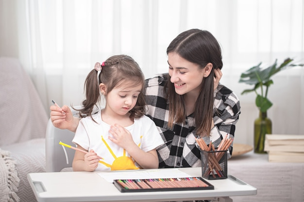 Young mother is doing homework with her little cute daughter. home schooling and education concept.