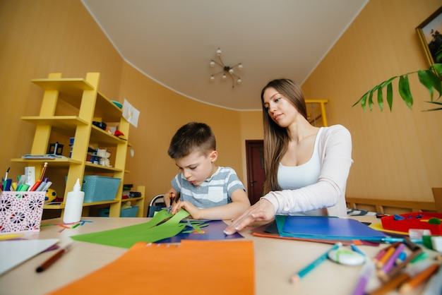A young mother is doing homework with her son at home. parents and training.