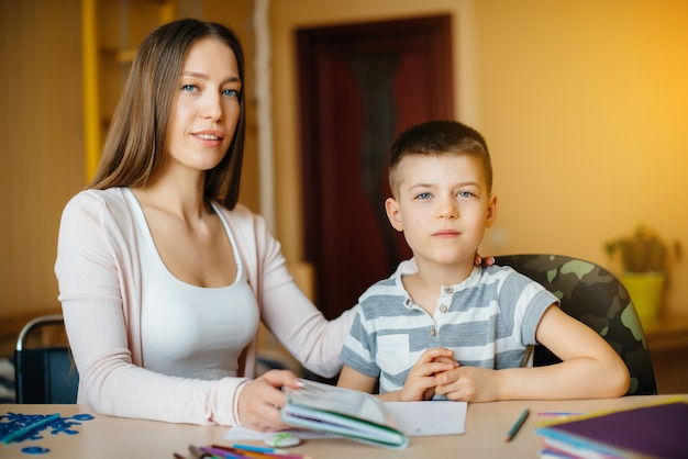 A young mother is doing homework with her son at home