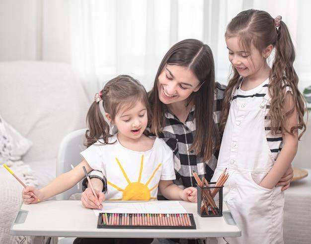 Молодая мама делает домашнее задание с маленькими дочками. концепция домашнего обучения и образования.