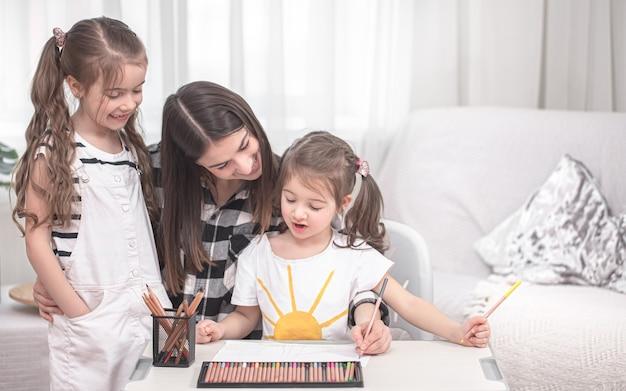 若い母親は小さな娘たちと宿題をしている。ホームスクーリングと教育の概念。