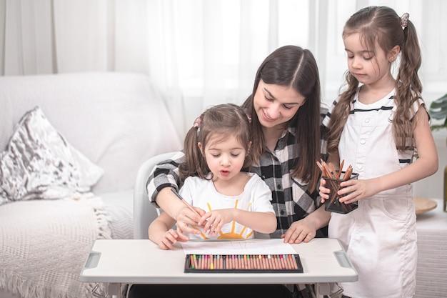 젊은 어머니는 작은 딸과 함께 숙제를하고 있습니다. 홈 스쿨링 및 교육