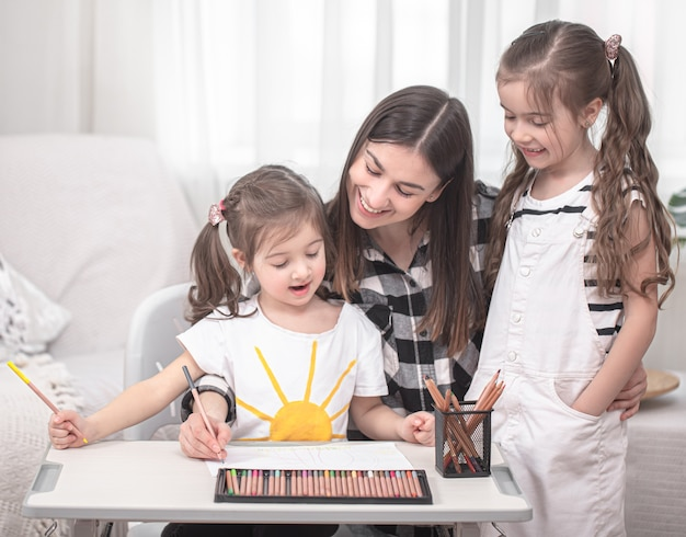Young mother is doing homework with little daughters. home schooling and education concept.