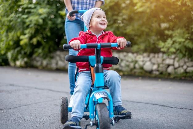 若い母親が散歩に幼児の男の子と子供の三輪車を押してください。