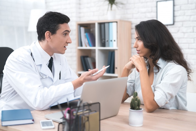 A young mother is talking to a doctor in his doctor's office