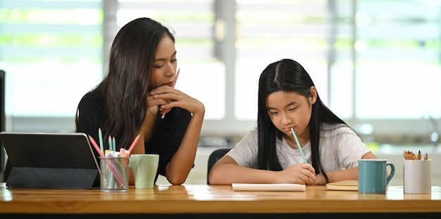 A young mother is teaching a daughter to do homework at the wooden table.