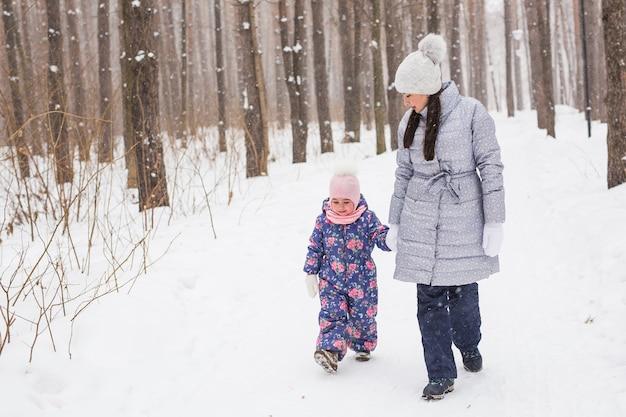 젊은 어머니는 겨울 숲에서 그녀의 딸과 함께 걷고있다