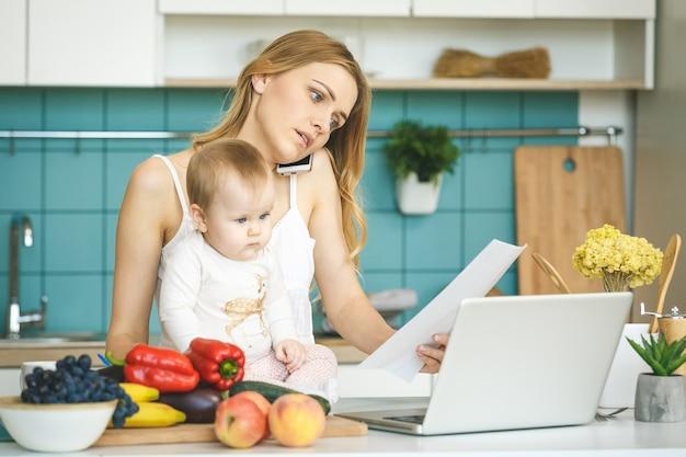 若い母親が在宅勤務しています。料理とモダンなキッチンの設定で彼女の赤ん坊の娘と遊ぶ。ラップトップを見てください。