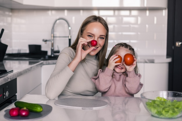 Young mother and kid preparing healthy food and having fun in the kitchen