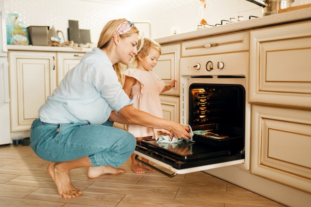 Young mother and kid remove from the oven baking sheet with chocolate pastry.