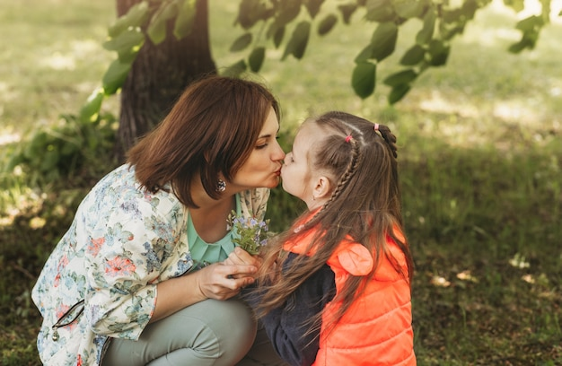 Молодая мать целует дочь в парке летом. концепция счастливой семьи, отношения матери и ребенка