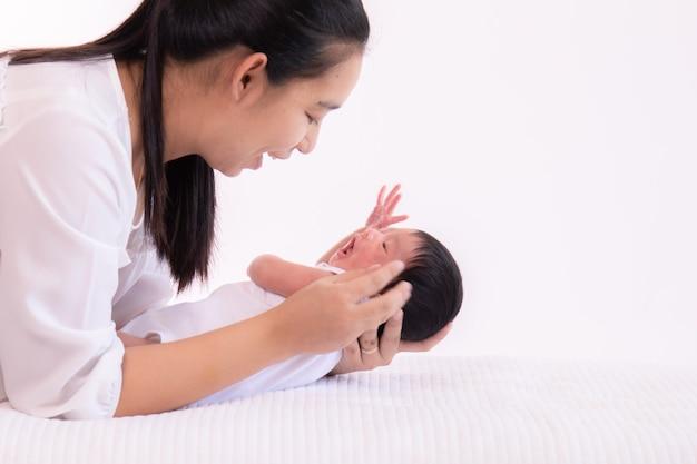 Молодая мать целует и держит крошечную очаровательную новорожденную девочку