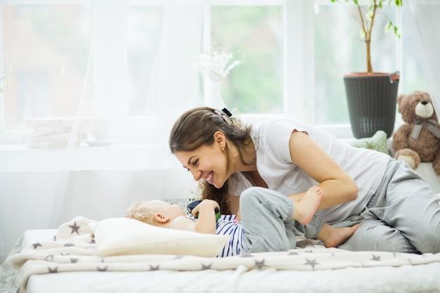 Молодая мать целует своего ребенка, лежа на кровати