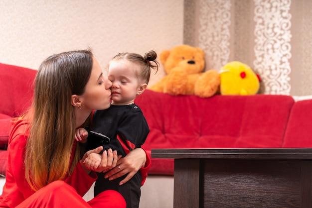 家で彼女の小さな女の赤ちゃんにキスする若い母親