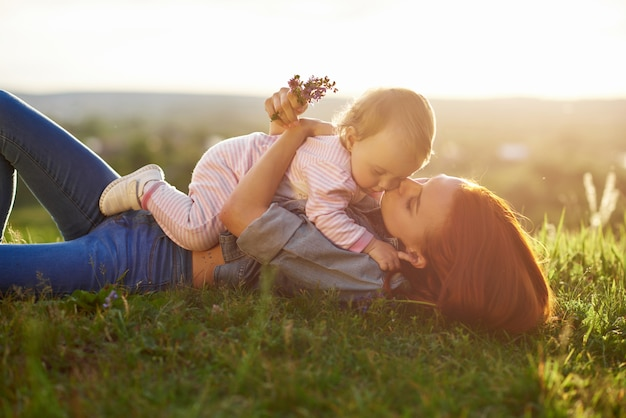 Young mother kissing little daughter lying on grass.