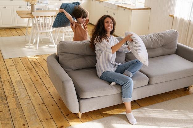 若い母親は家で就学前の息子と遊ぶ笑いママまたは乳母は小さな男の子と枕投げを楽しむ