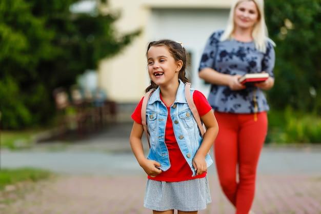 Молодая мама ведет дочь в школу