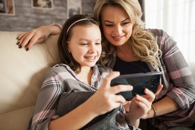 リビングルームのソファに座っているスマートフォンでアプリケーションを使用するために中かっこで幼い娘を学ぶ若い母親。