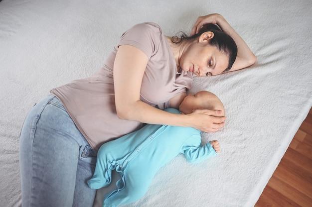 Молодая мама лежит с новорожденным милым младенцем в синем комбинезоне на кровати, обнимает и кормит его грудным молоком