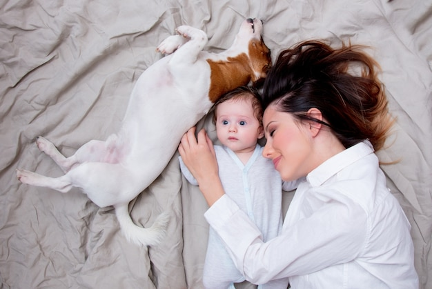 Young mother and a little child with dog lying down on bed