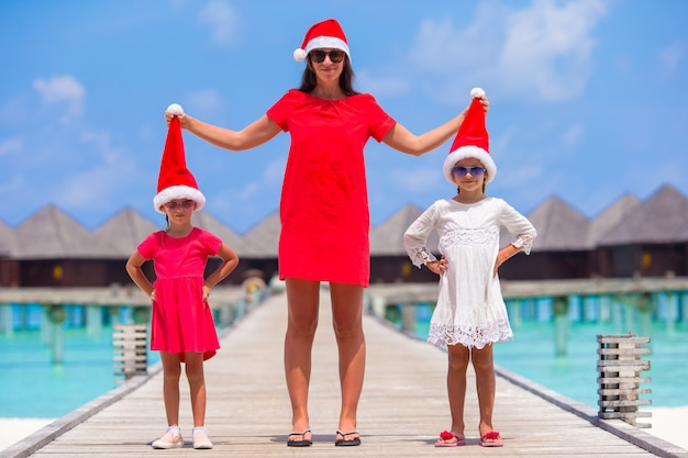 Young mother and little girls in santa hat