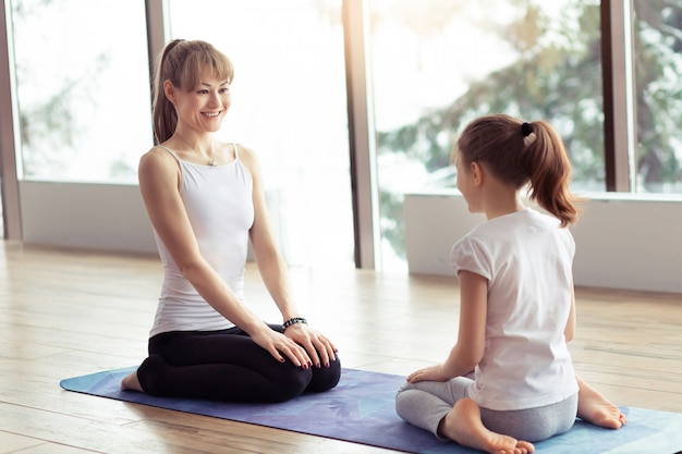 Young mother and little kid doing yoga or stretching fitness exercise together