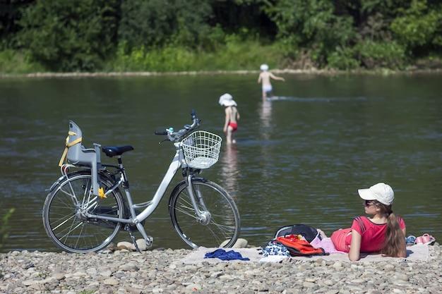 川のほとりで子供たちの世話をする若い母親