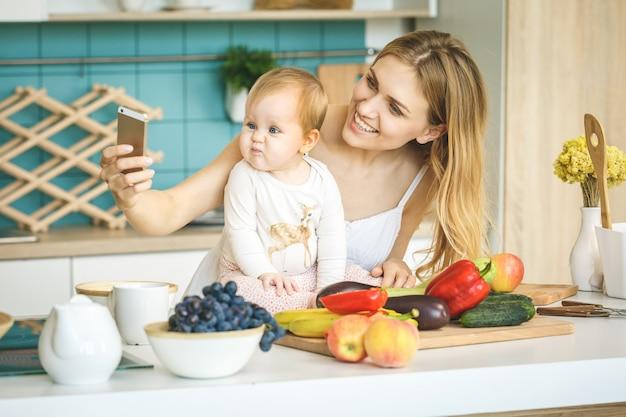 カメラ目線と笑顔、料理、モダンなキッチンの設定で彼女の赤ん坊の娘と遊ぶ若い母親。