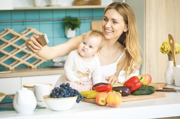 カメラ目線と笑顔、料理、モダンなキッチンで彼女の赤ん坊の娘と遊ぶ若い母親。電話を使って、自分撮りを作る。