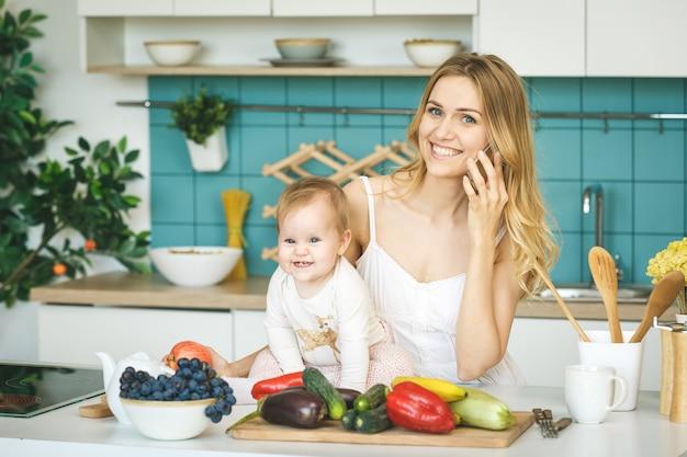 カメラ目線と笑顔、料理、モダンなキッチンで彼女の赤ん坊の娘と遊ぶ若い母親。電話を使用して。