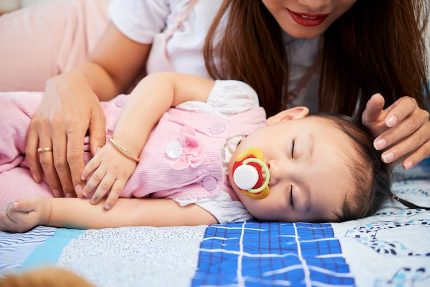 Young mother looking at baby girl with pacifier in mouth sleeping on bed