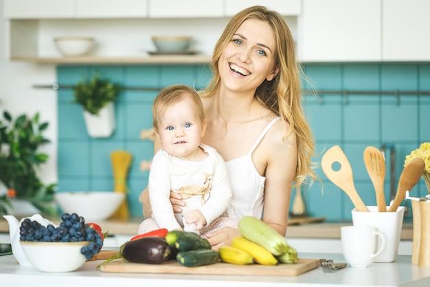 笑みを浮かべて探して、モダンなキッチンで彼女の赤ん坊の娘と遊ぶ若い母親