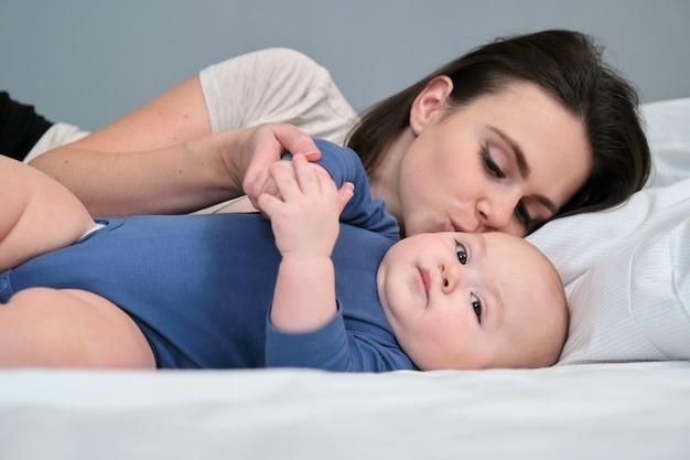 Молодая мама нежно целует своего малыша сына. женщина играет с ребенком, лежа в постели