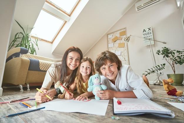 10代の息子と就学前の娘と一緒に居間の床に横たわっている若い母親と
