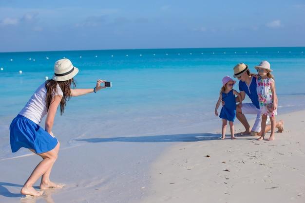 ビーチで彼女の家族の電話で写真を作る若い母親