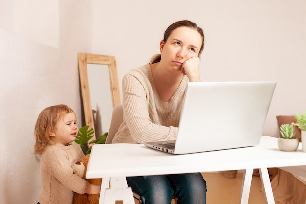 A young mother on maternity leave sits at a laptop and works.