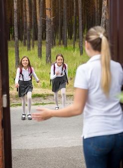 Молодая мать встречает своих дочерей после школы в дверях