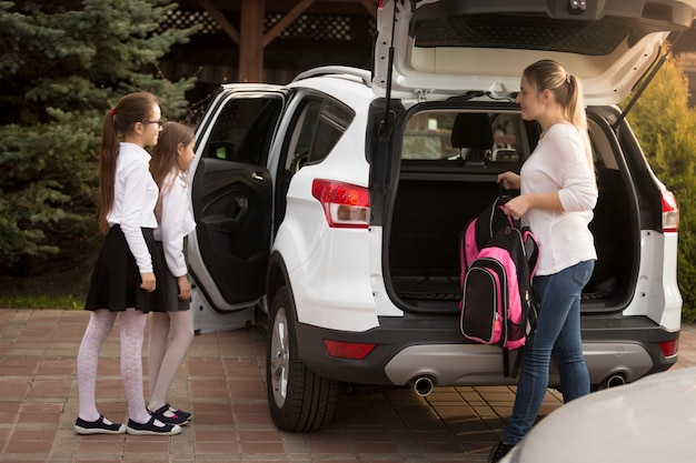 젊은 엄마는 방과 후 딸을 만나고 차 트렁크에 가방을 넣습니다.